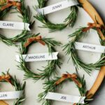Rosemary wreath place cards on a platter with a napkin.