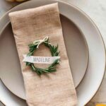 Rosemary wreath place cards on a napkin on a plates.