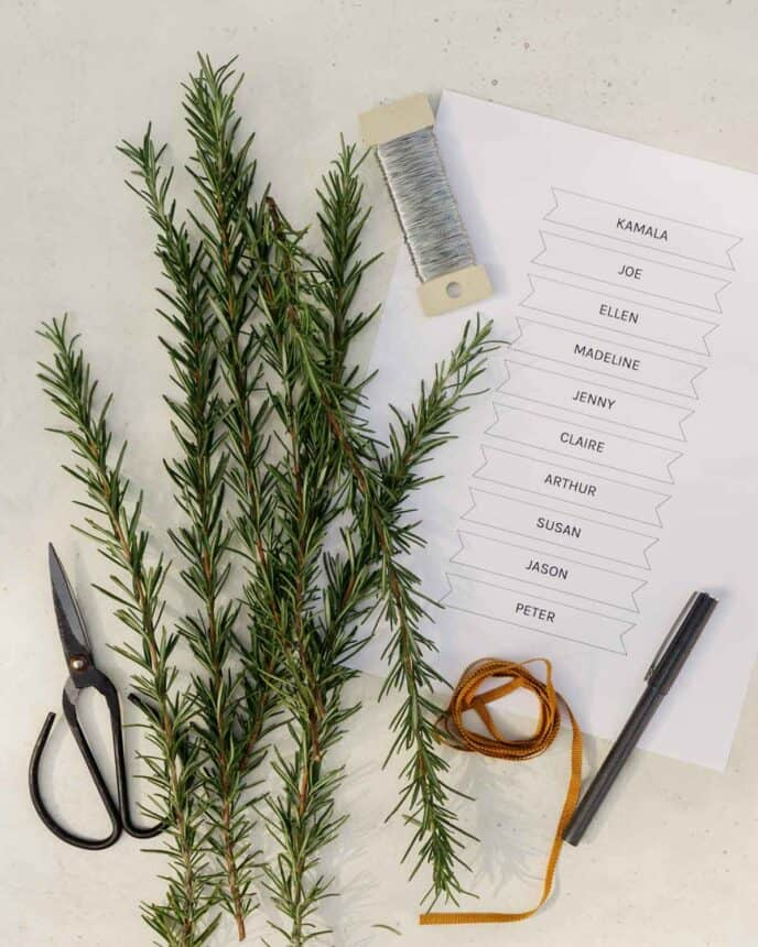 Supplies for rosemary wreath place cards on a surface.