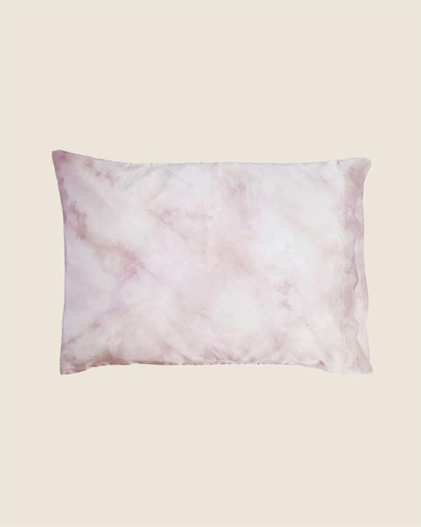 A rose colored tie dyed pillowcase on a tan background.
