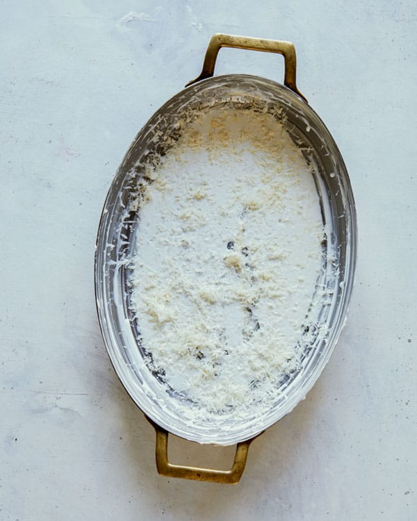 A buttered baking dish with a layer of cream, parmesan, and garlic.