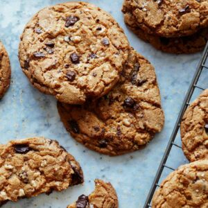 Salted Brown Butter Chocolate and Toffee Chips cookies on a surface with milk.