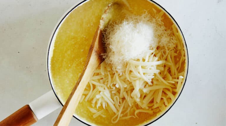 Polenta in a pot with cheese and a wooden spoon.