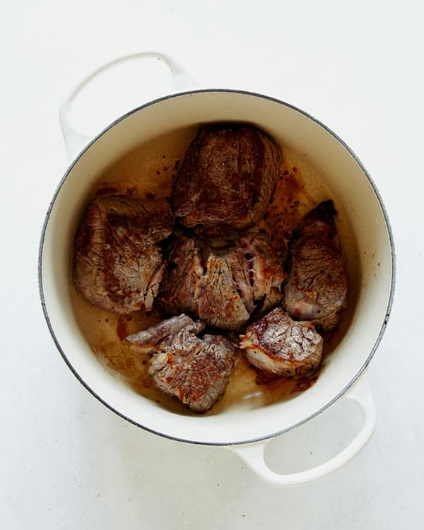 Seared beef in a stock pot overhead.