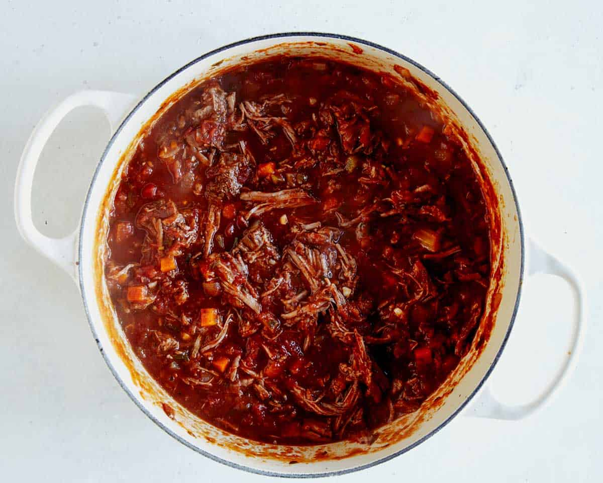 Braised beef shredded in a stock pot.