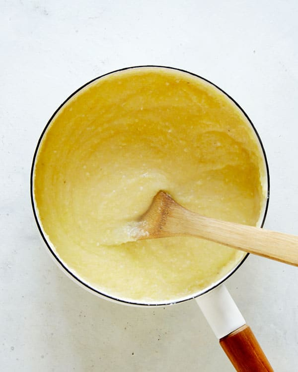 Polenta in a pot with a wooden spoon.