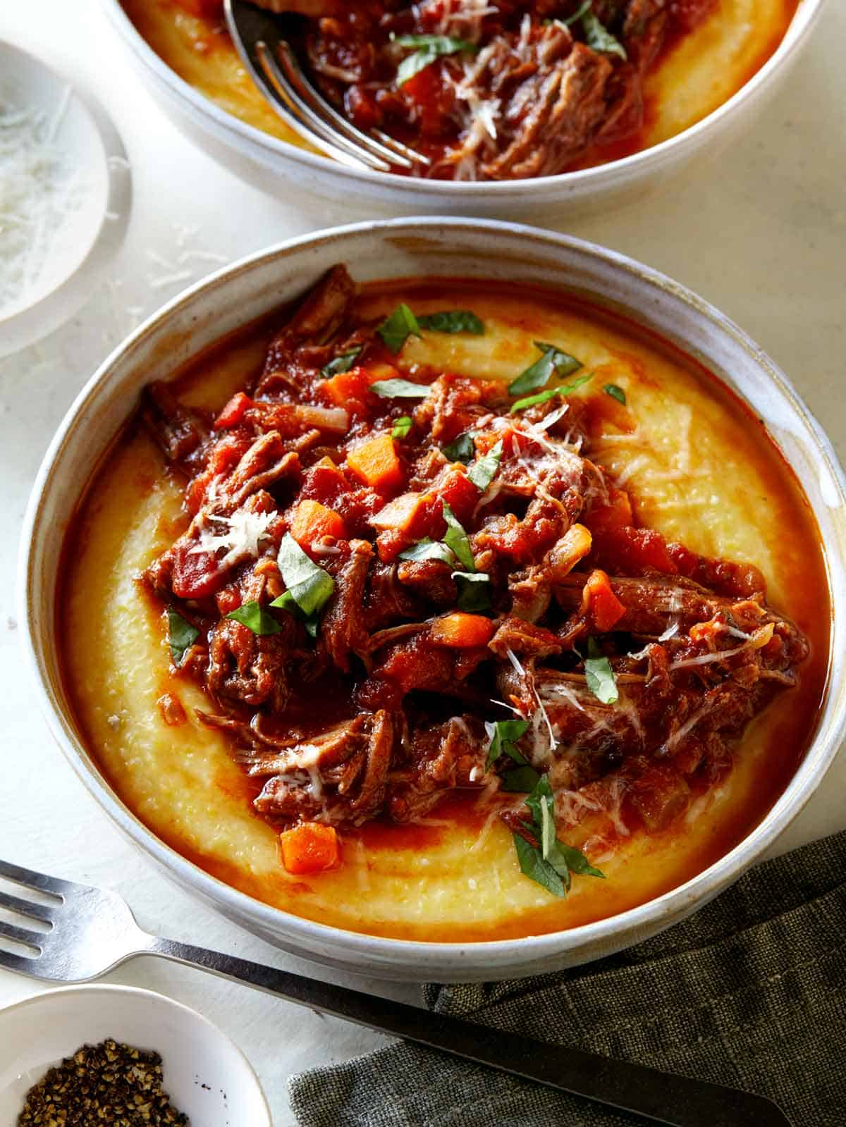 Braised beef ragu in two bowls with forks on the side.