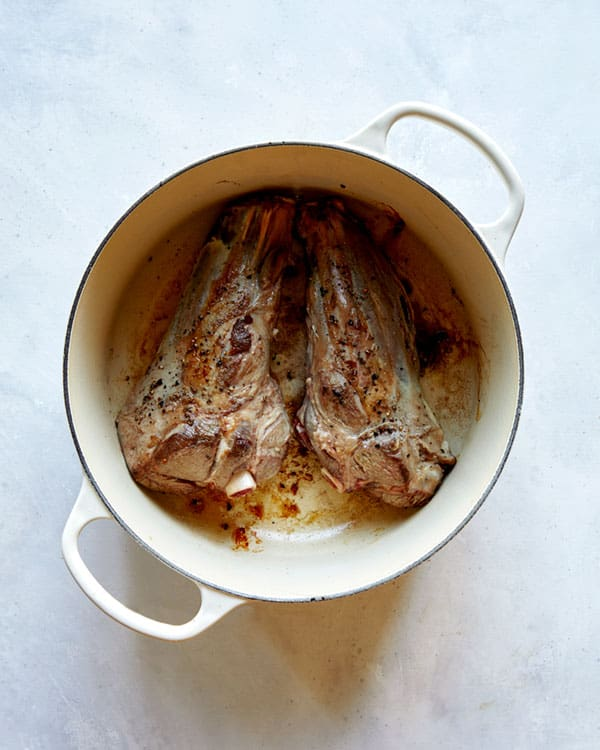 Sear lamb shanks in a stock pot.