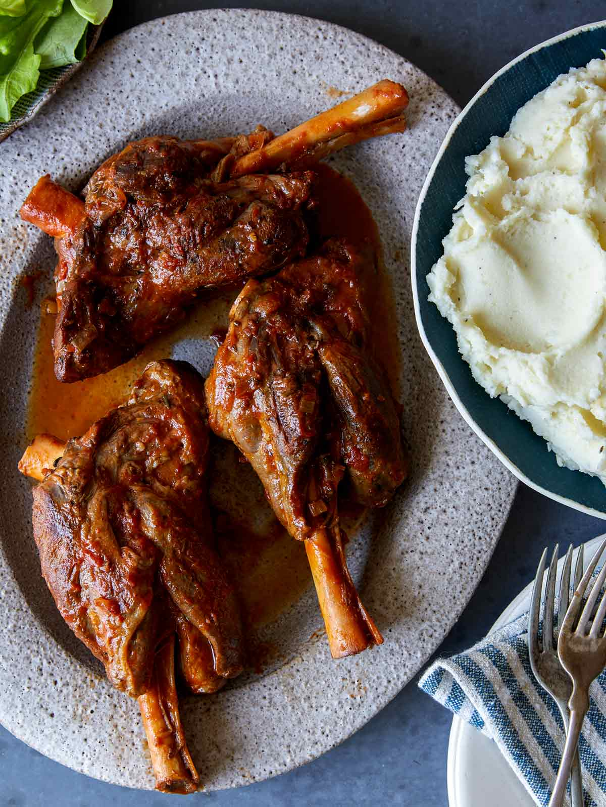 Braised Lamb shanks on a platter with mashed potatoes next to it.