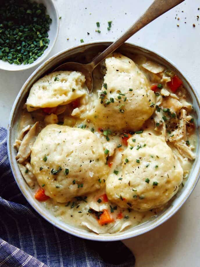 Chicken and Dumplings soup recipe in a bowl with a spoon taken a piece out of one of the dumplings.