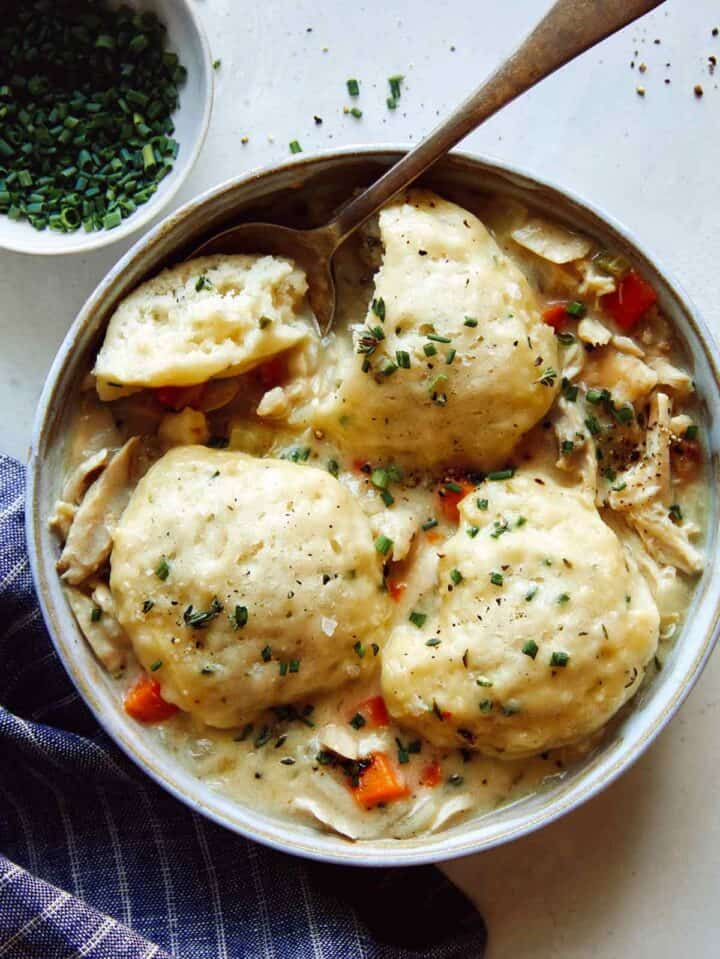Chicken and Dumplings recipe in a bowl with a spoon taken a piece out of one of the dumplings.