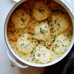 A pot of chicken and dumpling recipe with a napkin next to it.