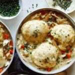 Chicken and dumplings recipe made in two bowls with garnishes on the side.