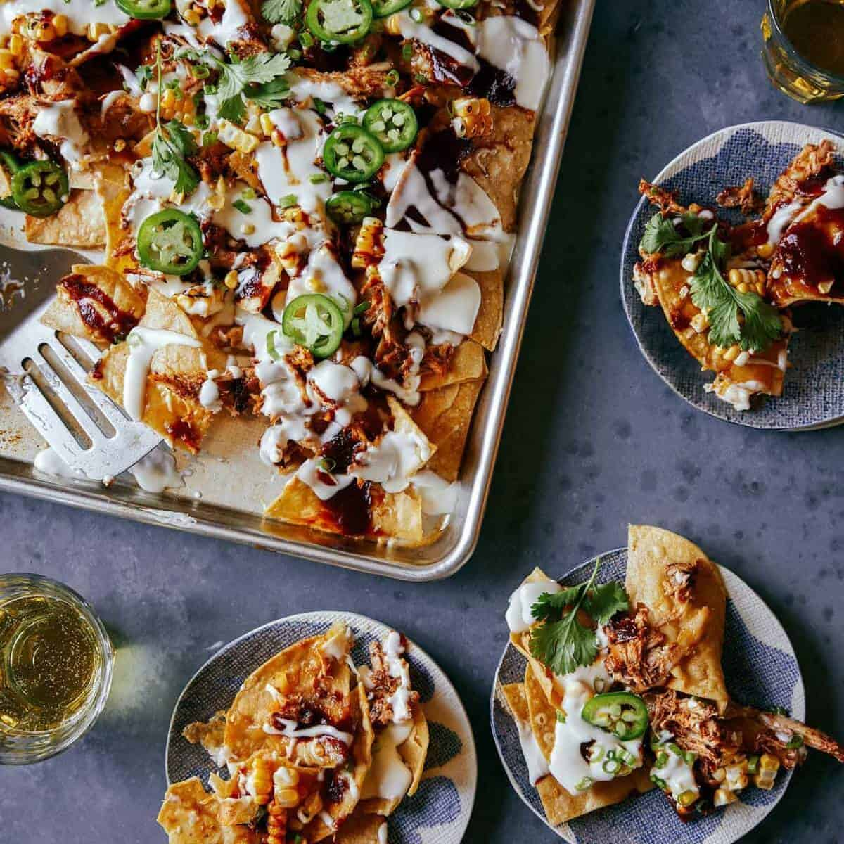 A sheet pan of chipotle chicken nachos with servings on small plates, a new years eve appetizer.