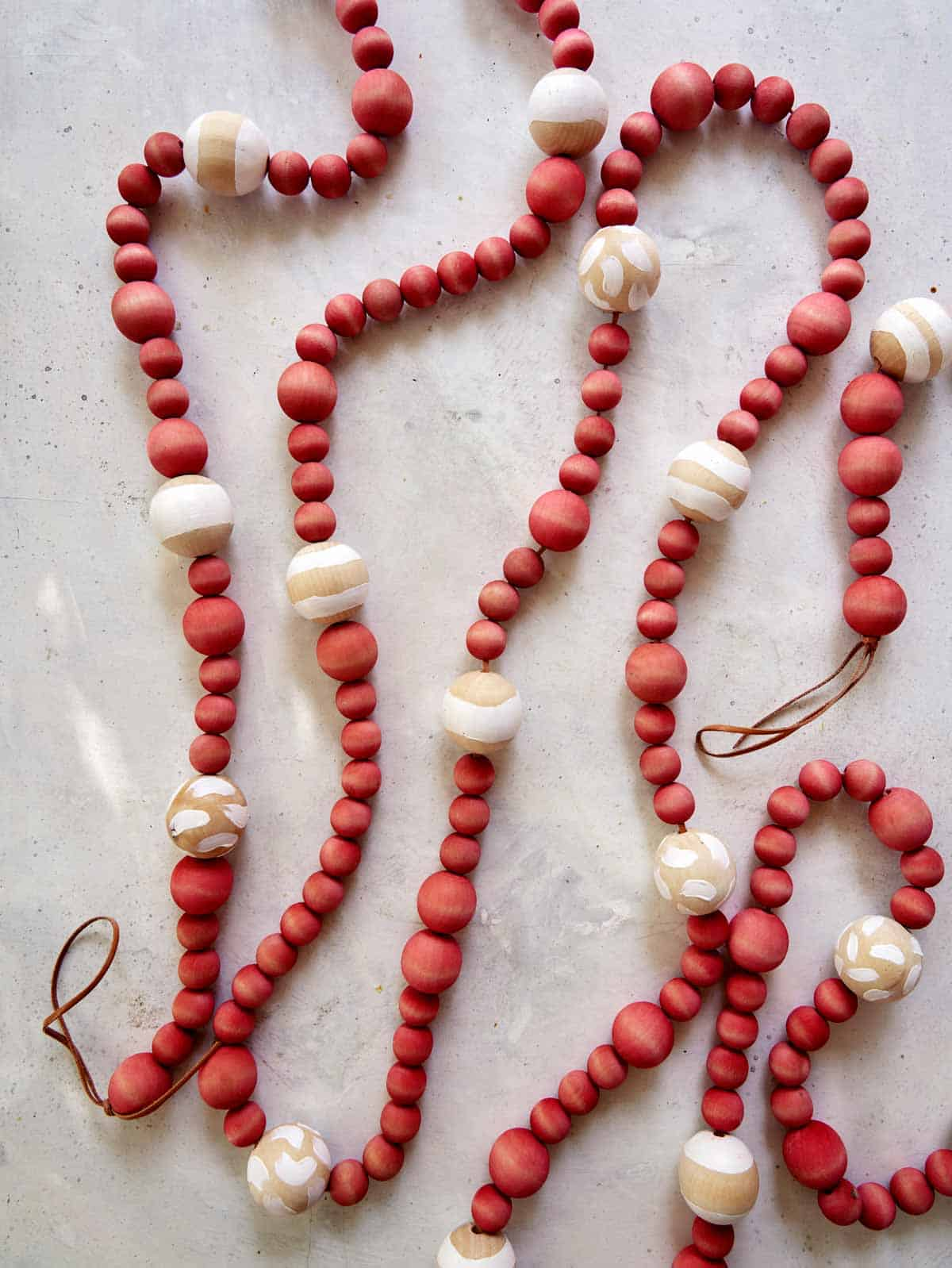 A wood bead garland laid out on a  counter.