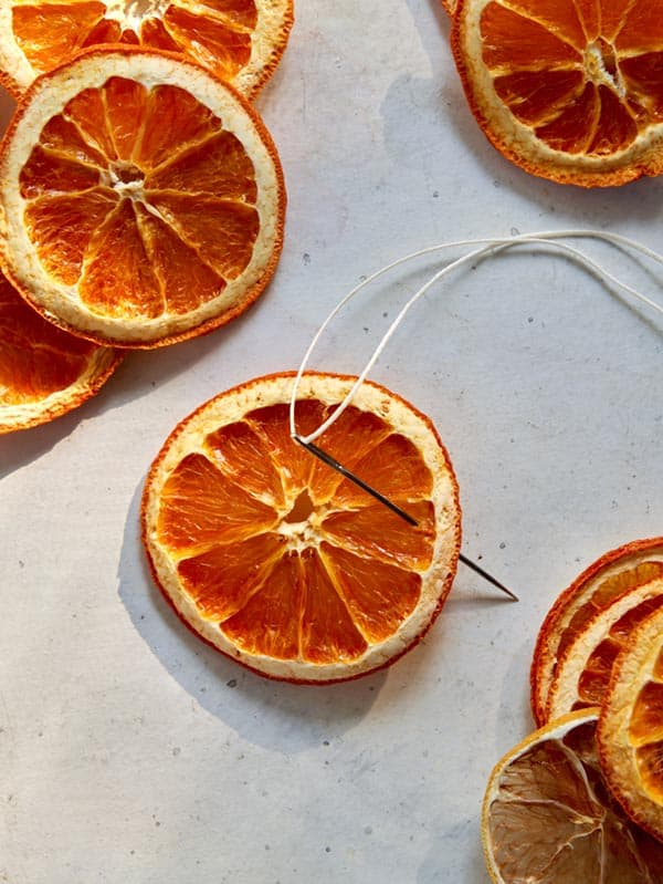 Making a citrus garland with a needle and twine.