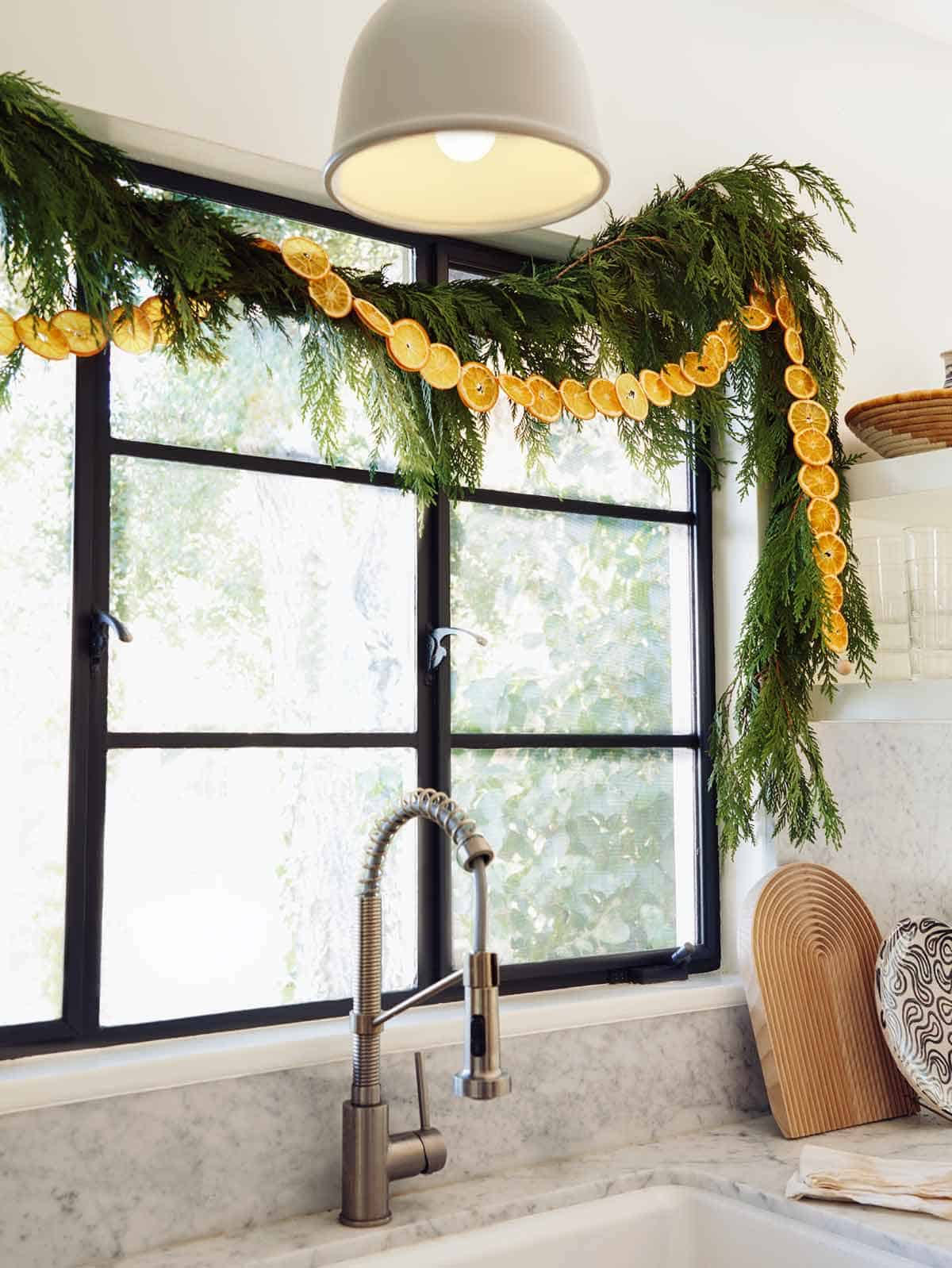 A dehydrated citrus garland strung up above a window in the kitchen.