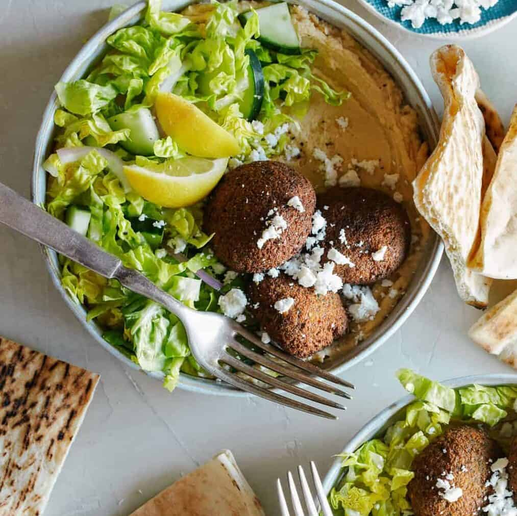 Falafel salad hummus bowls with forks and grilled pita bread, heathy  dinner recipe.
