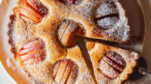 German Apple Cake on a platter with a slice out.