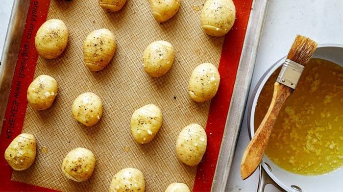 Basting hasselback potatoes.
