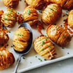 Cheesy Hasselback potatoes on a platter with a spoon.