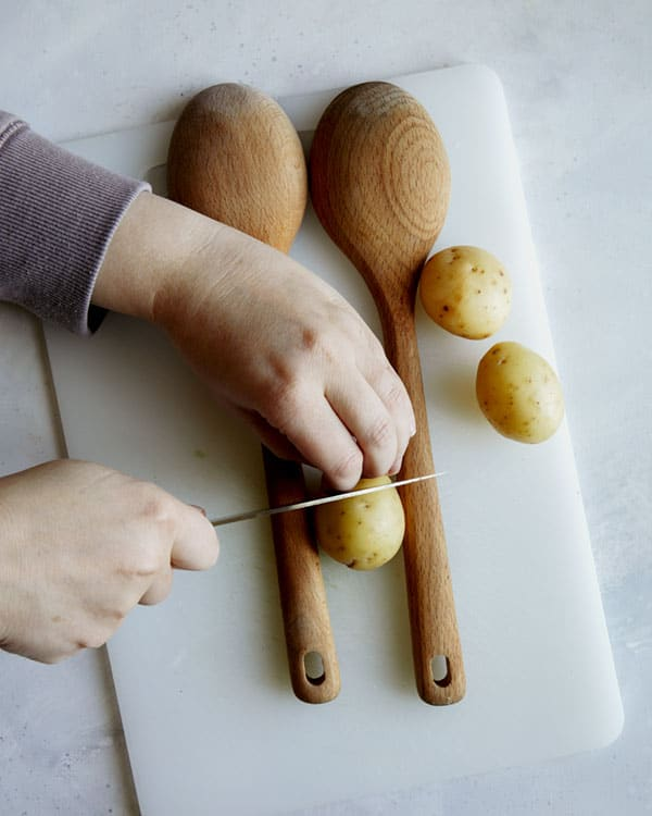 Cutting hasselback potatoes with wooden spoons.