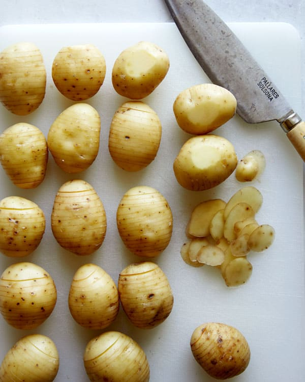Slicing the bottom of potatoes to make them level.