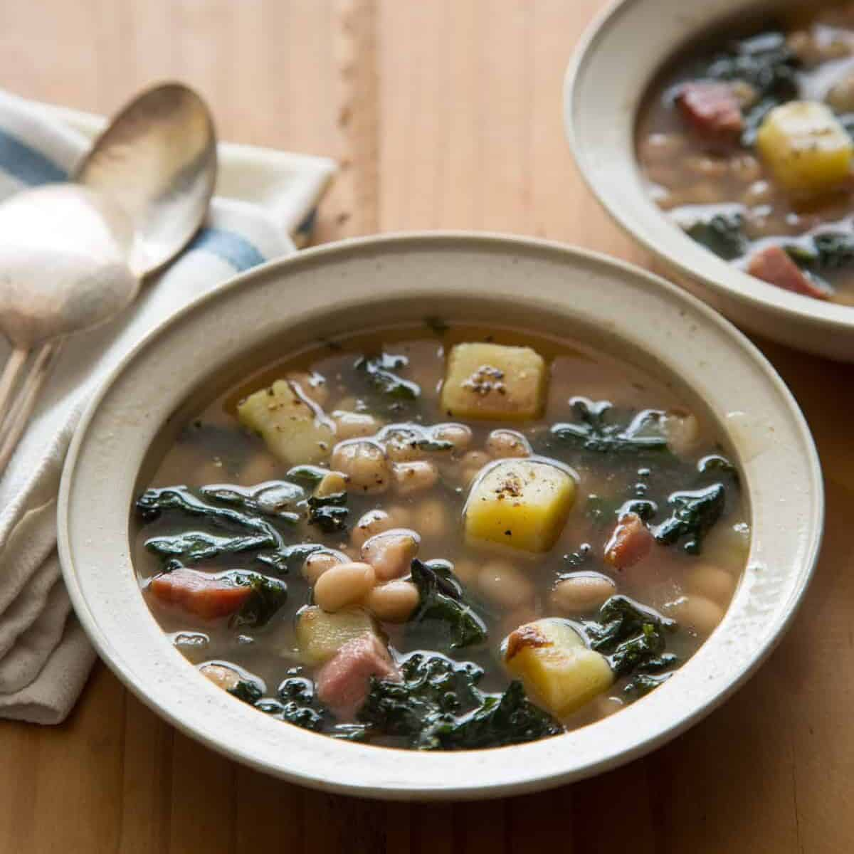 Heathy dinner recipe -  bowls of hearty white bean and kale soup with napkins and spoons.