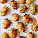 Hasselback potatoes with cheese on top and sprinkled with chives.
