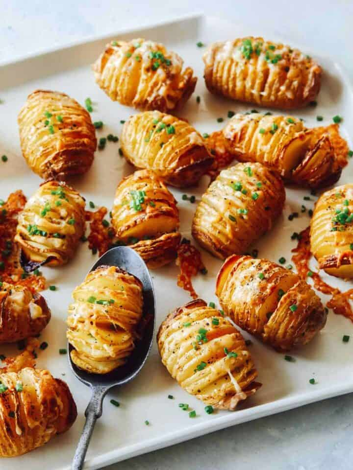 Hasselback potatoes on a platter with a spoon.