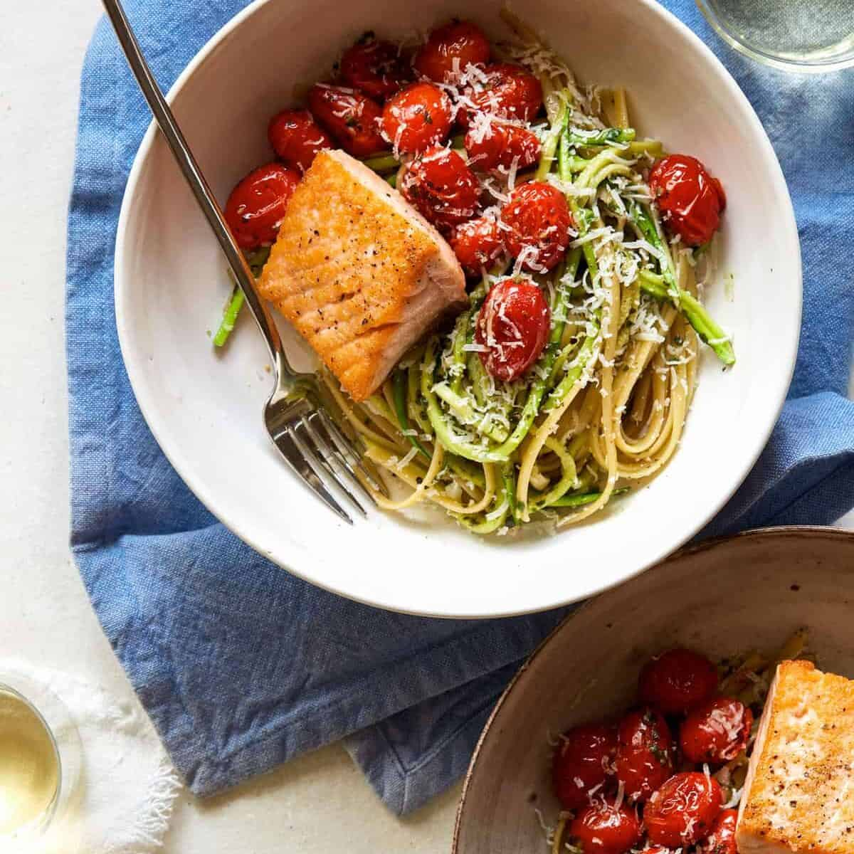 Seared salmon over 50/50 spaghetti with arugula and walnut pesto with a fork. Heathy dinner ideas.
