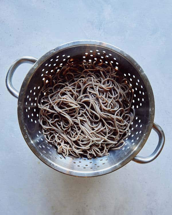 Boiled and drained soba noodles in a colander.