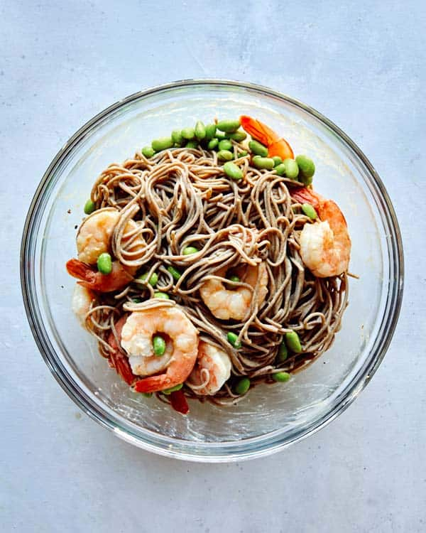 Soba noodles with shrimp in a glass bowl.