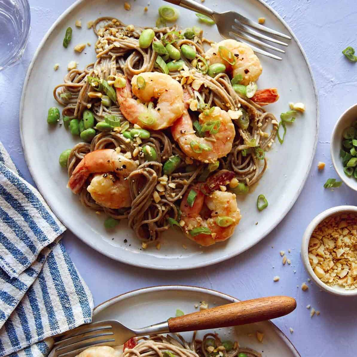 Shrimp and soba noodle recipe on two plates with sesame seeds on the side.