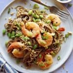 Close up on a soba noodle recipe with shrimp and a fork with it.