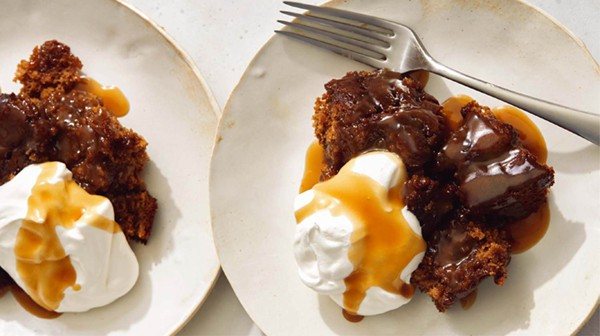 Sticky toffee pudding served onto plates with whipped cream and toffee sauce.