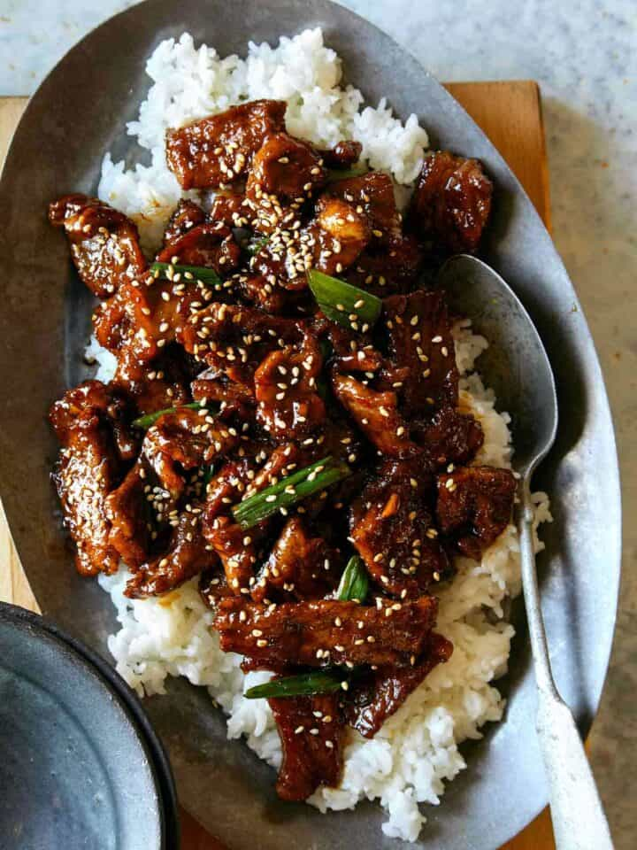 Mongolian beef recipe on a platter with a spoon in it, a dinner idea.