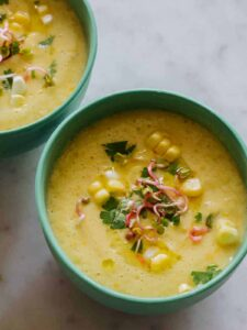 A close up of bowls of sweet corn gazpacho with spoons.