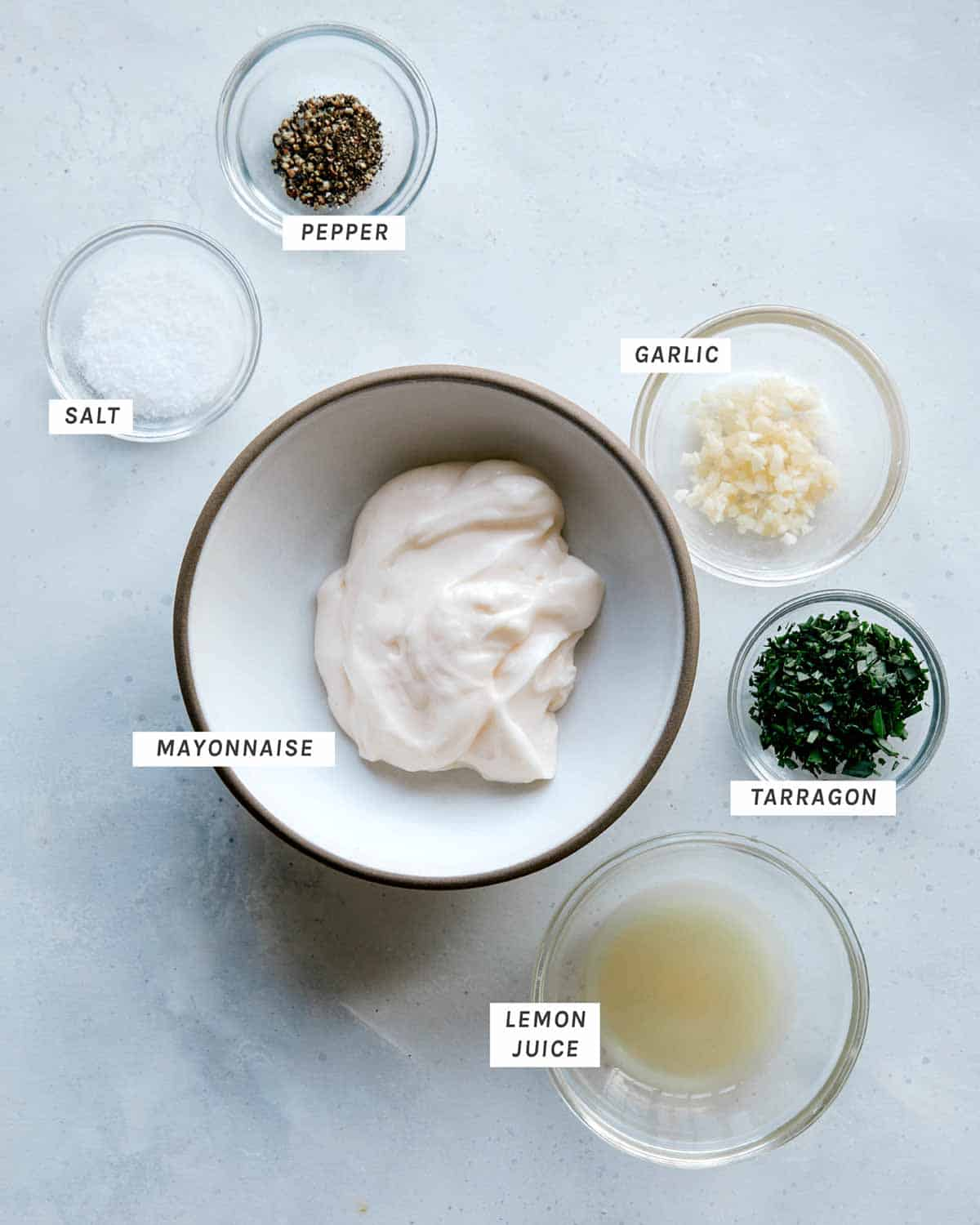 Ingredients for a tarragon aioli all laid on on a kitchen surface.