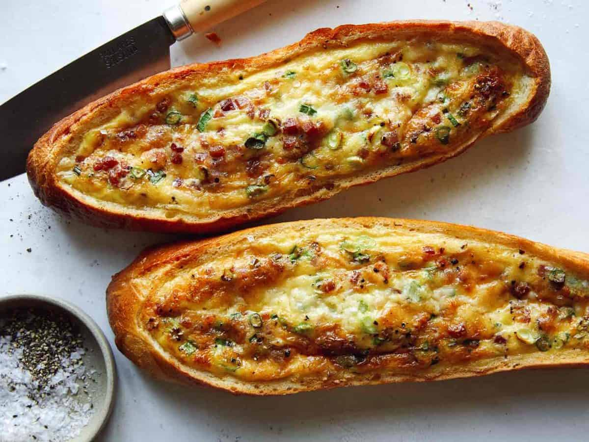 Baked egg boats on a surface with a knife.