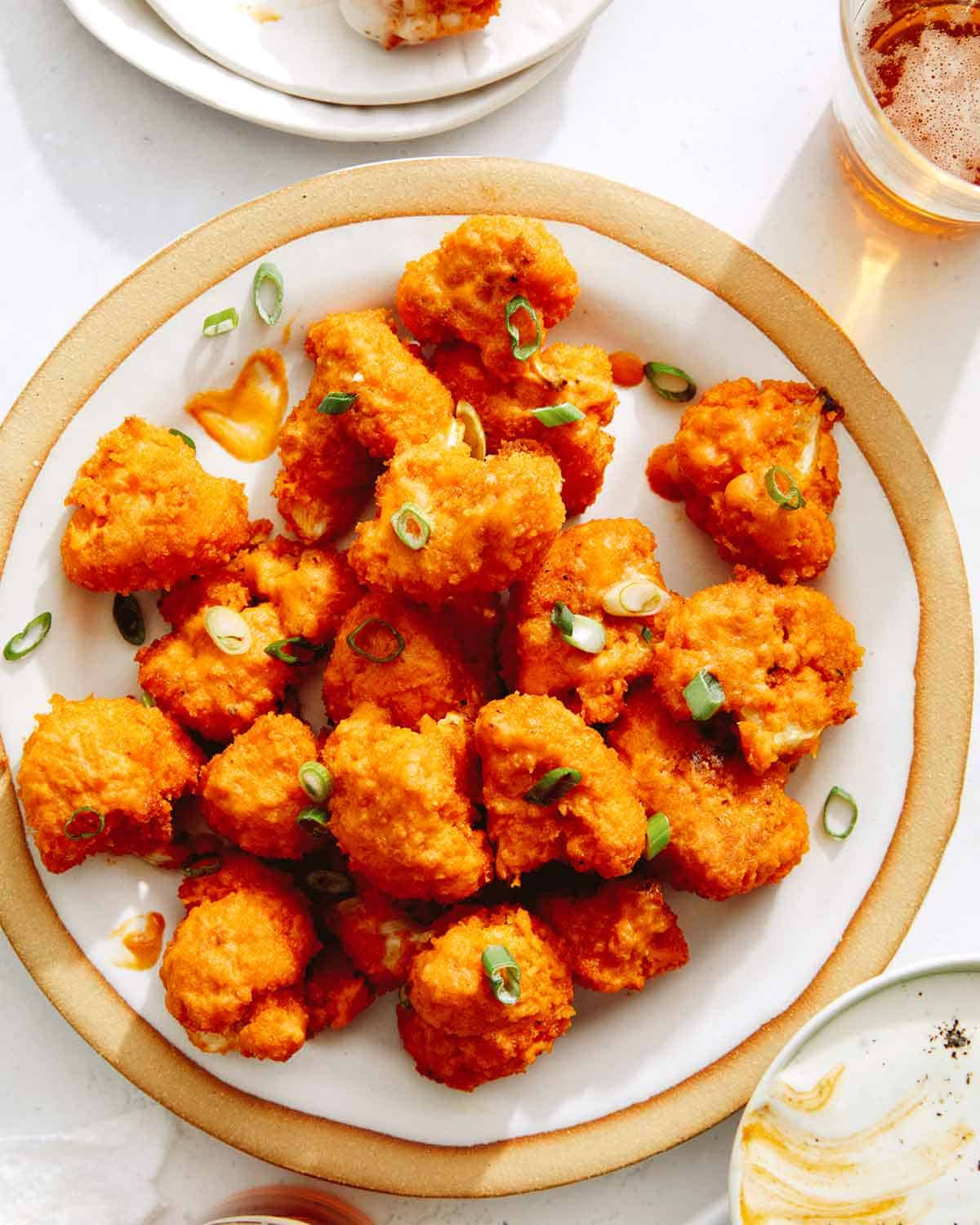 Buffalo cauliflower on a plate with green onions and beer on the side.