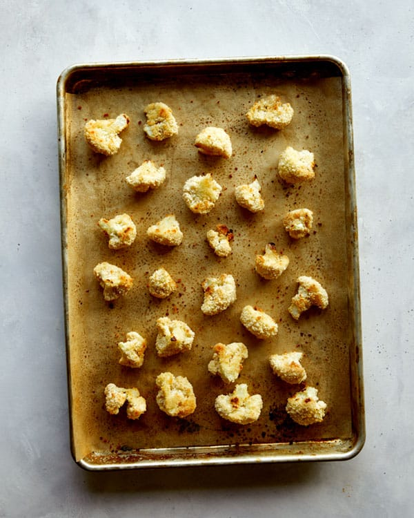 Cauliflower florets baked on a baking sheet for buffalo cauliflower.