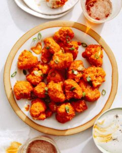 Buffalo cauliflower recipe on a plate with beers next to it.
