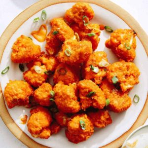 Buffalo cauliflower on a place with dipping sauce next to it.