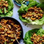 Chicken lettuce wraps with lettuce and chicken in them on the side.