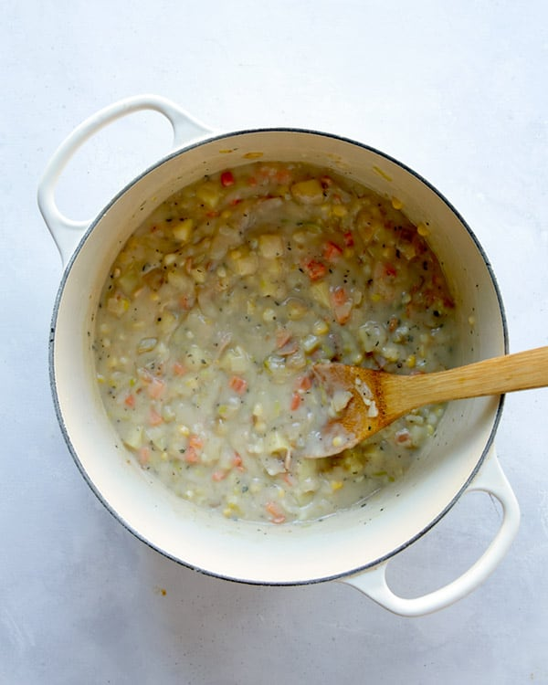 Clam chowder in a pot cooking down with stock.