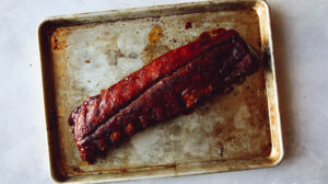 Sticky oven baked ribs on a a baking sheet ready to be cut up.