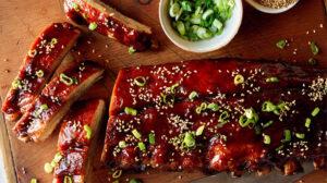 Honey hoisin oven baked ribs on a cutting board.