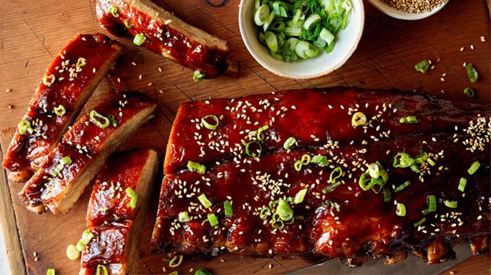 Honey hoisin oven baked ribs on a cutting board.