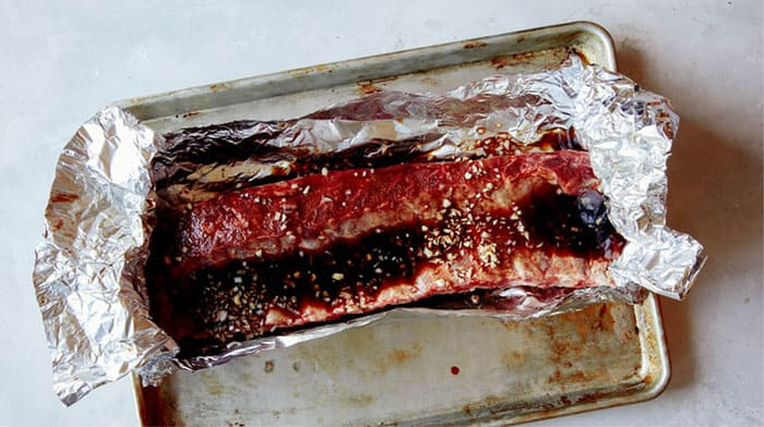 Oven baked ribs with marinade in tin foil